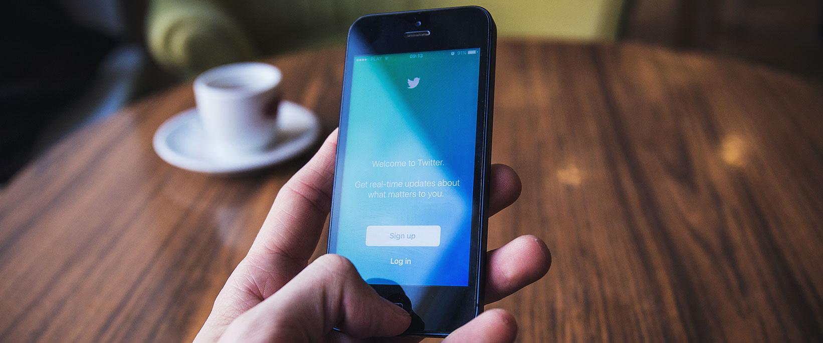 En hand som håller en telefon för att logga in på Twitter