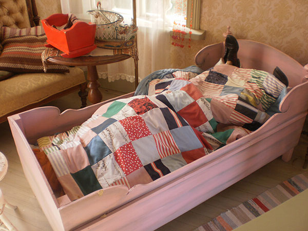 Pippi Långstrump som ligger i sin säng med fötterna på huvudkudden